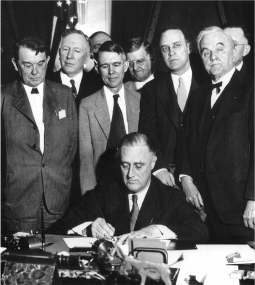 Franklin Roosevelt sits at a desk and signs a document. A group of men stands behind him.
