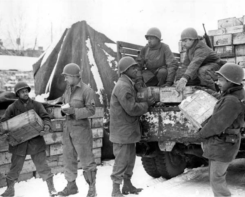 A group of African American soldiers load boxes onto the back of a truck in the snow.