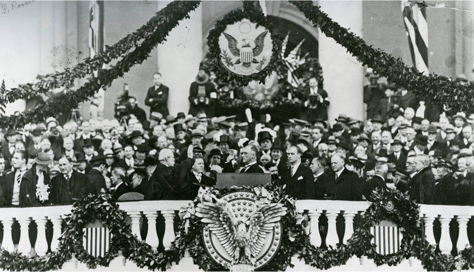 Franklin D. Roosevelt stands in front of the capitol with his right arm raised. A crowd surrounds him. The capitol is decorated with garland and American seals.