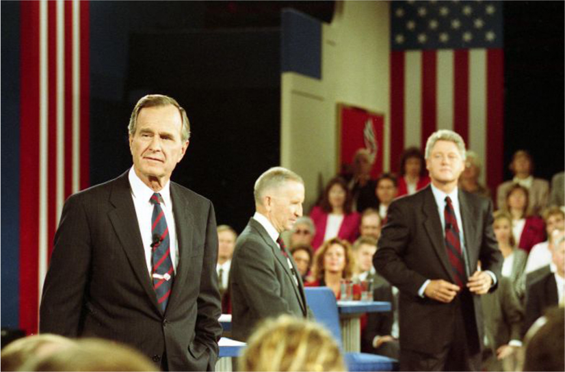 President H.W. Bush, Ross Perot, and Bill Clinton stand on a stage and look out over the crowd.