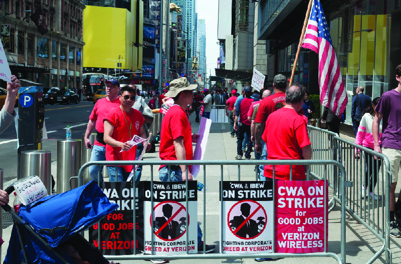 """This image shows a group of people dressed in matching red shirts in an area enclosed with signs that say """"CWA on strike for good jobs at Verizon Wireless"""" and """"CWA and IBEW on strike. Fighting corporate greed at Verizon."""""""