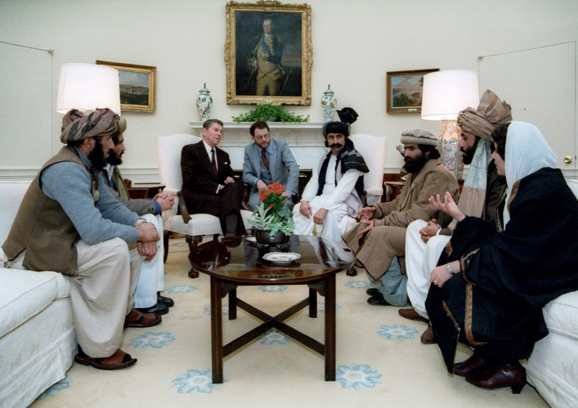 President Reagan and mujahideen leaders sit on couches and chairs in the White House.