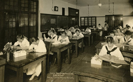 Early 20th century black and white photo showing female students at their desks.