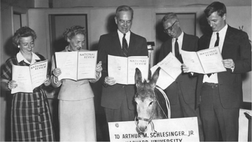 A group of people stand around a donkey while holding copies of the National Review. A sign in front of the donkey reads