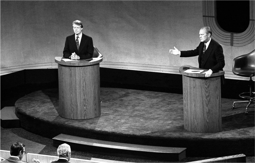 Jimmy Carter and Gerald Ford stand on a stage behind podiums. Gerald Ford gestures to Jimmy Carter as he speaks.