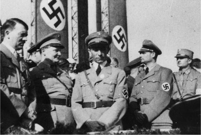 A group of men in German uniforms stand in front of Nazi flags. Adolf Hitler is seen on the left.