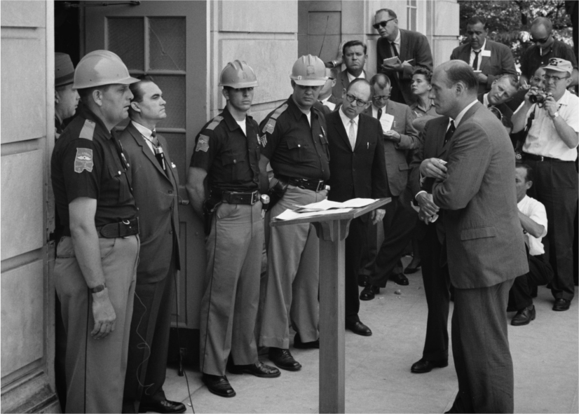 Governor George Wallace stands in the doorway. Other officers stand next to him. Attorney General Nicholas Katzenbach stands in front of him. A crowd of reporters are in the background.